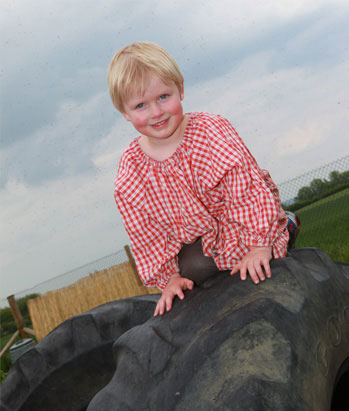 Montessori nursery child climbing on tyres
